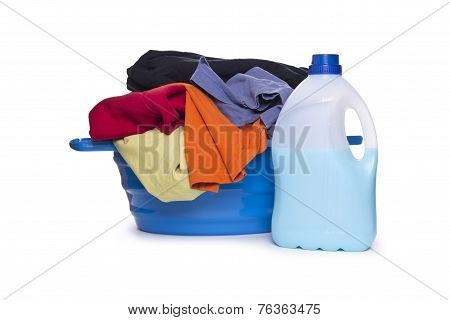 Laundry basket full of dirty clothes and fabric softener and champion on a white background