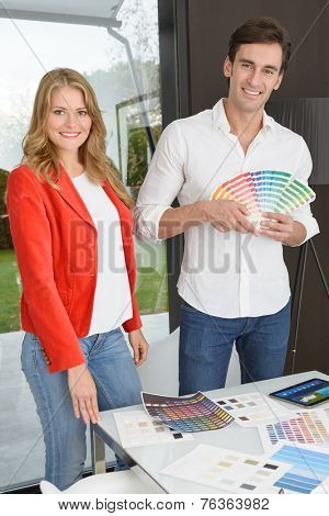 Man and woman in an office surrounded by color charts, material samples and technology