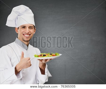 Chef cook with vegetable salad dish thumbs up, grey background