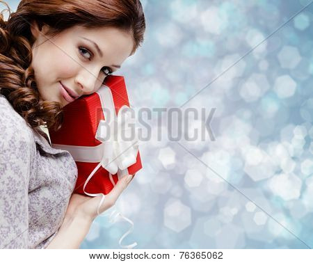 Young woman is satisfied with a birthday gift wrapped in red paper, blue background