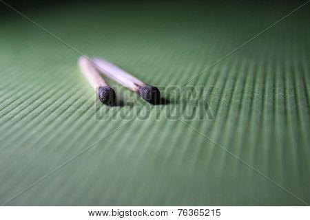 Burnt Matchstick On A Green Fabric