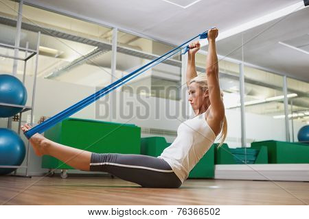 Full length side view of a young woman using resistance band in fitness studio