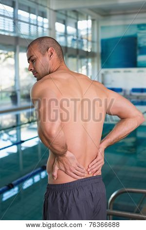 Rear view of a shirtless fit swimmer with back ache by the pool