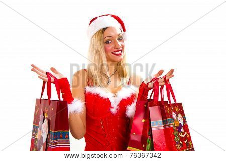 Cheerful Christmas Woman In Santa's Wear Smiling And Holding Shopping Bags