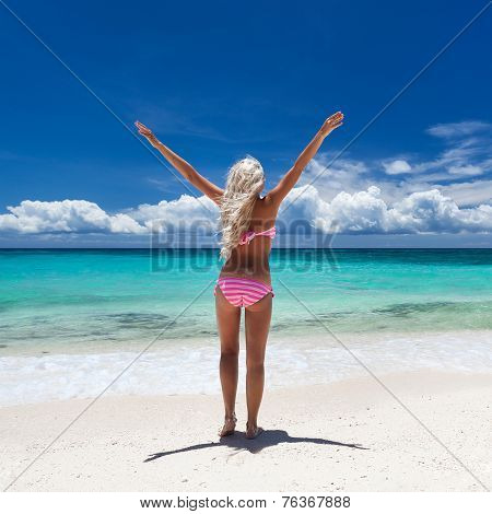 Woman standing with hands up on tropical beach
