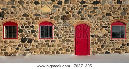 Old Stone Barn With Bright Red Door And Three Windows