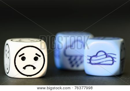 Concept Of Sad Autumn Weather - Emoticon And Weather Dice On Black Background
