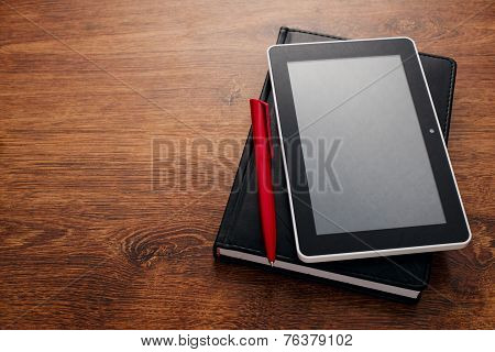 Pen And Tablet On Top Of Closed Book At The Table