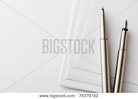 Pens And Blank Papers On Top Of White Table