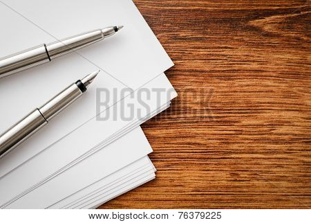 Pens And Sheets On Wooden Table With Copy Space
