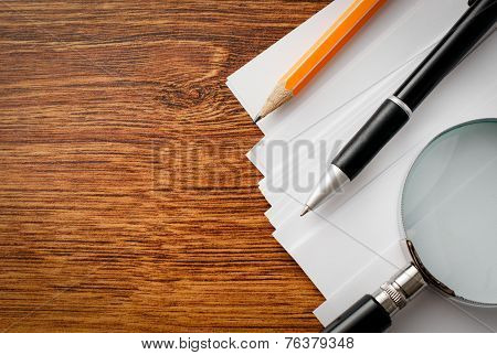 Conceptual Supplies And Magnifying Glass On Table