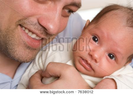 Father Holding Hands On Newborn