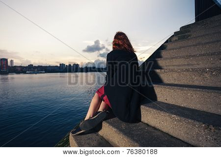 Woman Sitting On Stairs By River At Sunset