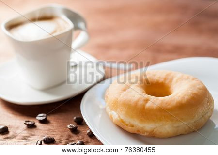 Doughnut With Cup Of Coffee In Background.
