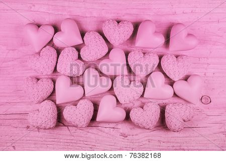 Pink wooden background for valentines day with a collection of hearts.