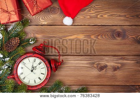 Christmas background with clock, snow fir tree and gift boxes over wood