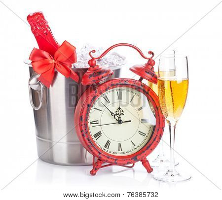 Two champagne glasses, bottle in cooler and clock. Isolated on white background
