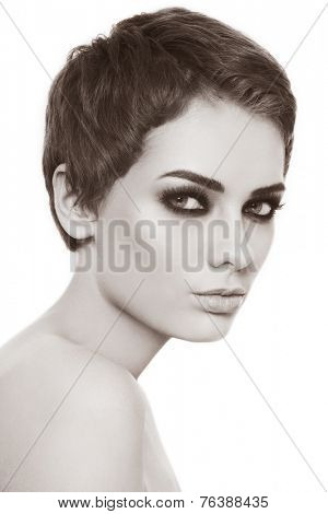 Sepia portrait of young beautiful woman with stylish haircut and smokey eyes