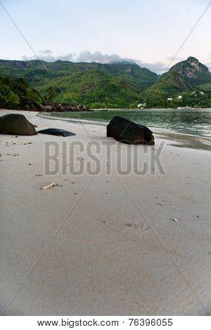 Medium Size Rocks on White Beach Sand with Green Morne Blanc Mountain Afar, Located at Mahe Island Seychelles.