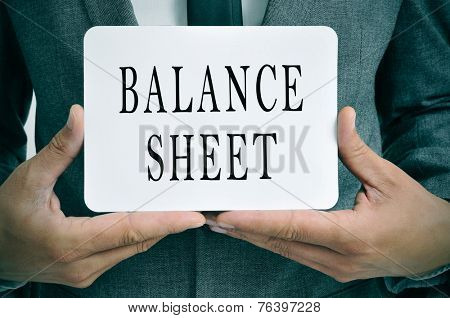 a businessman showing a signboard with the text balance sheet written in it