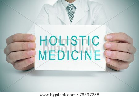 a doctor showing a signboard with the text holistic medicine written in it