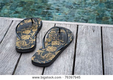 Decorative floral slip slops on a wooden pool deck overlooking the mottled blue-green water conceptual of a summer vacation