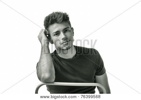 Attractive Young Man Sitting, Leaning On Back Of A Chair