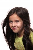 stock photo of 7-year-old  - Pretty long haired brunette seven year old girl smiling on white background - JPG