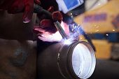 foto of pipe-welding  - welder in factory with protective equipment welding metal pipes