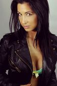 picture of low-necked  - beautiful brunette with a leather jacket on a gray background - JPG