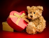 image of mating bears  - A brown teddy bear sitting and hugging a heart shaped box with a bow ribbon isolated against a red and black background - JPG