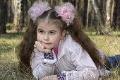 stock photo of hair bow  - Spring in the forest lies on the grass girl with long hair and big bow and thinks about that - JPG