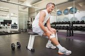 image of knee  - Injured man gripping his knee in the weights room at the gym - JPG
