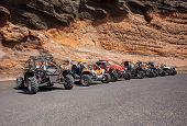 picture of buggy  - Several buggies are parked in a row in front of a wall of rock - JPG