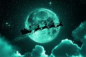 pic of stelles  - Santa flying in his sleigh against a full moon background with stars and clouds - JPG