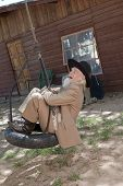 stock photo of tire swing  - A senior man in a western style suit and hat is laughing and swinging on a tire swing. Vertical shot.
