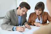 stock photo of rental agreement  - Young couple in real estate agency signing property agreement - JPG