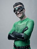 foto of cross-dressing  - Cheerful superhero in green costume smiling with arms crossed - JPG