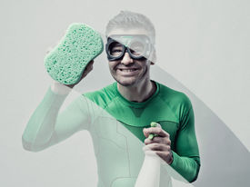 stock photo of detergent  - Smiling superhero cleaning with sponge and detergent - JPG