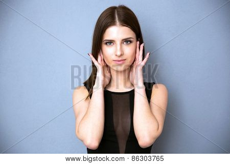 Portrait of a cute woman looking at camera over gray background