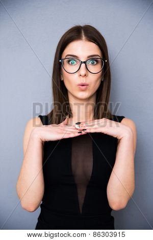 Portrait of a surprised cute woman in fashion black dress. Posing over gray background. Looking at the camera