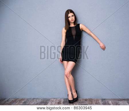Full length portrait of a cute attractive woman in sexy fashion dress. Posing over gray wall. Looking at camera