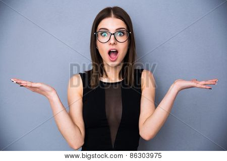 Young beautiful woman with facial expression of surprise standing over gray background. Wearing in trendy black dress and glasses. Looking at the camera