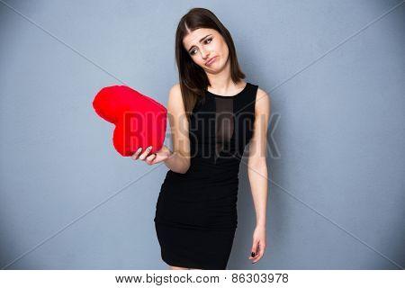 Portrait of a woman in sexy black dress holding red heart. Standing over gray background. Looking on red heart