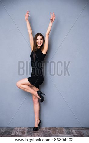 Full length portrait of a laughing cute woman in fashion black dress. Posing over gray background. With raised hands up. Looking at camera.