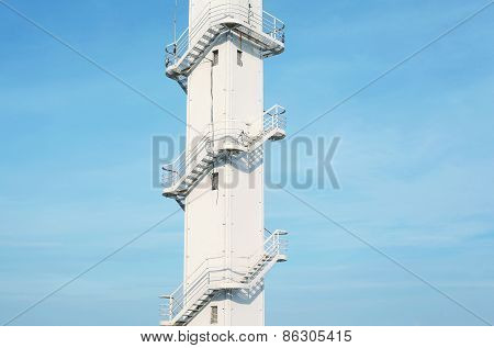 Architectural Fragment Of The White Tower With A Metal Spiral Staircase Against The Blue Sky