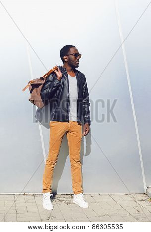 Outdoor Fashion Portrait Of Handsome African Man In Black Leather Jacket With Bag Standing Against T