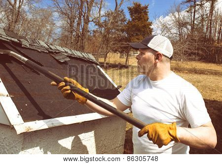Man taking shingles off a shed roof