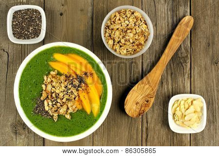 Green smoothie bowl overhead scene on wood
