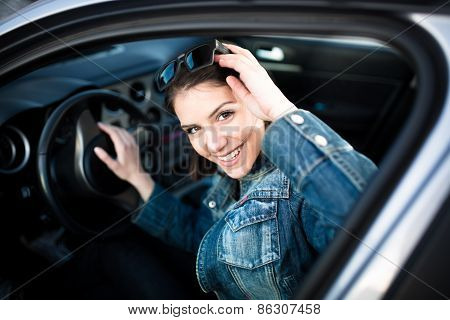 Happy woman in new car.Young woman in car going on road trip.Driver license exam